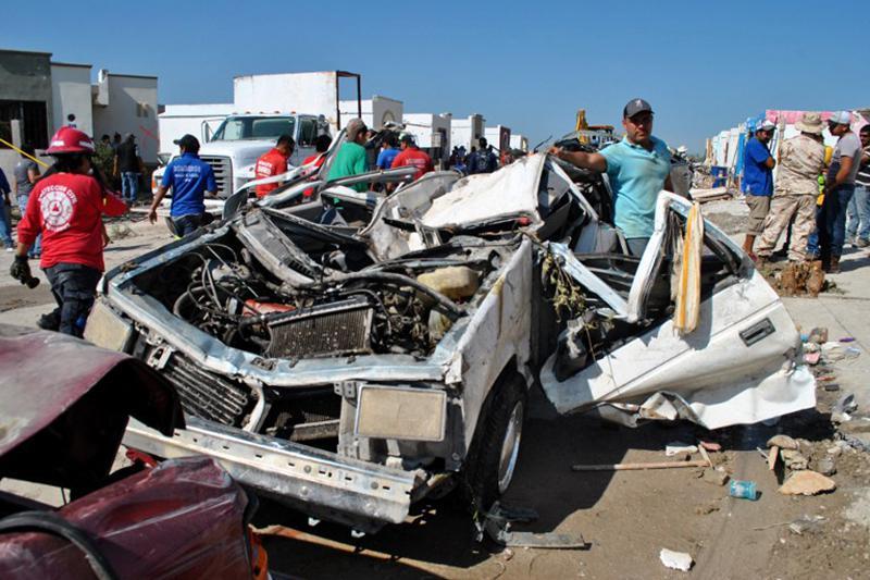 Хозяин позирует на фоне раскоряченной машины после прохождения торнадо в Мексике