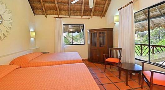 Просторный семейный номер отеля Allegro Playacar с двумя двуспальными кроватями имеет шикарный вид из окна на тропический сад.