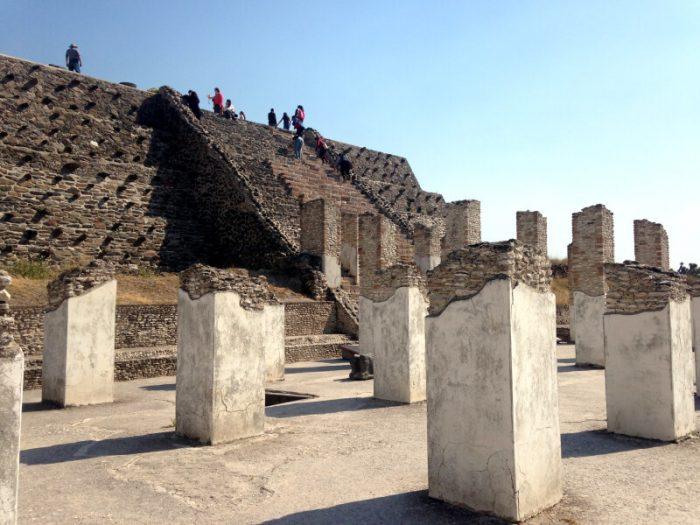 Развалины колонн с барельефами на фоне главной пирамиды тольтеков