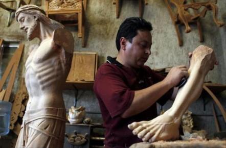 Работник по дереву изготавливает статую Христа. Мексика