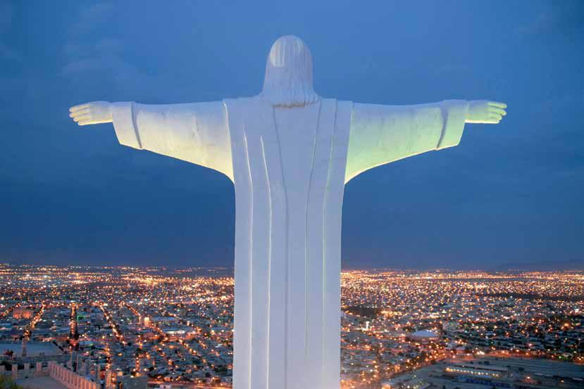 Статуя Христа с раскинутыми руками обращена на вечерний город Торреон, штат Коауила, Мексика