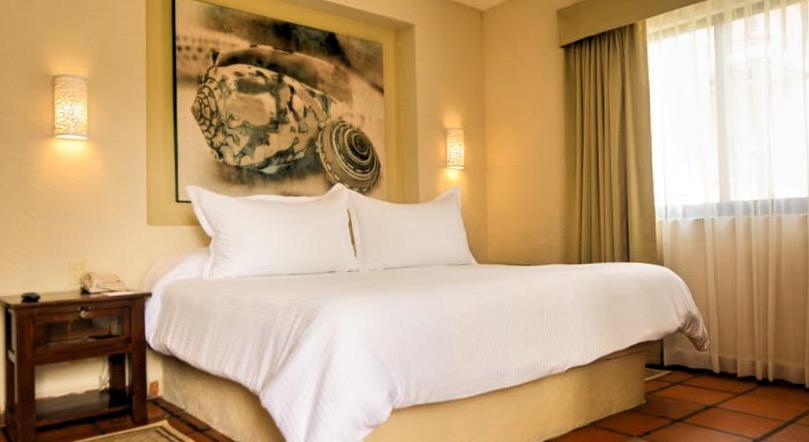 Изумительный и комфортный номер отеля Allegro Playacar включает замечательную двуспальную кровать и спокойный уютный интерьер.